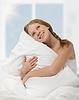梦幻般的美丽女孩抱着枕头坐在床上时, | 免版税照片
