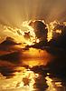 Escena puesta de sol espectacular con nubes oscuras y rayos sobre el mar | Foto de stock