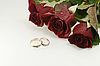 Two wedding rings with three red beautiful roses | Stock Foto