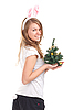 Girl dressed as rabbit with Christmas tree in the hands | Stock Foto