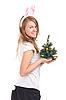 女孩打扮成兔子的圣诞树在手中 | 免版税照片