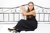 美丽的女孩穿着,坐在床上 | 免版税照片