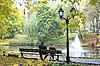 男人和女孩在秋季公园的长凳上   免版税照片