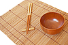 Chopsticks with wooden bowl on bamboo mat | Stock Foto
