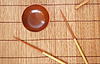 Chopsticks with wooden bowl on bamboo mat   Stock Foto