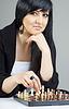 Una hermosa mujer joven morena jugando al ajedrez en casa | Foto de stock