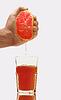 Glas Grapefruitsaft und Hand mit der Hälfte der | Stock Photo