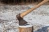 Hacha y registro en bosque de invierno | Foto de stock