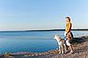 Frau mit einem Hund am Meer | Stock Foto