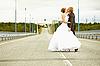 Newlyweds kissing passionately on highway   Stock Foto