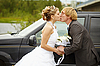 Bride and groom kissing near car | Stock Foto