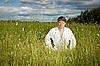 Young man in white kimono sits in grass | 免版税照片