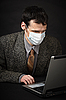 Man in medical mask diagnoses computer | Stock Foto