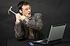 Hombre joven furioso rompe ordenador martillo | Foto de stock