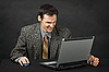 Furious man sits at table and looks at laptop screen | Stock Foto
