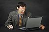 暴怒的人,坐在桌上,并在笔记本电脑屏幕上看起来 | 免版税照片