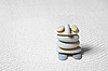 Funny little man made from stones on sand | Stock Foto