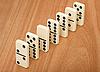一行七多米诺骨牌的木制表面 | 免版税照片