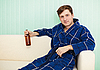 Young man drinks beer in dressing gown on sofa | 免版税照片
