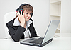 Woman in ear-phones with laptop | Stock Foto