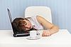 年轻女子睡在笔记本电脑键盘上的工作场所 | 免版税照片