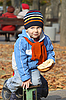 Photo 300 DPI: Cheerful boy with the bread playing in park