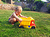 Kid plays with toy in the grass | Stock Foto