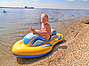 Photo 300 DPI: Joyful kid on the shore in an inflatable boat.