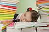 十几岁的女孩睡在摞书 | 免版税照片