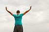 Фото 300 DPI: Молодой человек пребывания с поднятыми руками на синем небе