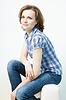 有吸引力的年轻女孩坐在沙发上家 | 免版税照片