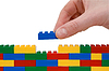 Hand building wall of toy blocks | Stock Foto