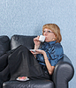 沙发上的女人喝咖啡 | 免版税照片