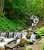 瀑布跌倒在长满青苔的岩石 | 免版税照片
