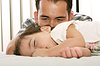 그녀가자는 동안 아버지는 그의 아름다운 아기를보고 | Stock Foto