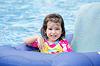 Niña que se divierte en flotador azul tropical en | Foto de stock