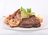 Steak and shrimp dinner over plaid tablecloth | Stock Foto