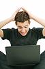 Фото 300 DPI: Молодой человек потрясен чем-то он видит на своем ноутбуке