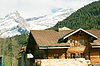 Lovely Swiss chalet with mountains in background | Stock Foto