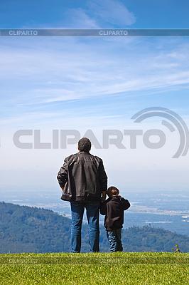 Отец и сын смотрят вдаль со скалы. | Фото большого размера |ID 3018728