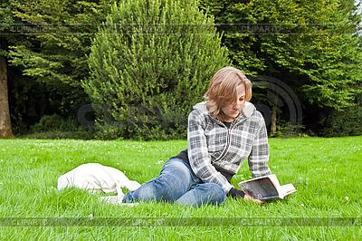 Młoda dziewczyna czytanie książki na trawie | Foto stockowe wysokiej rozdzielczości |ID 3019339