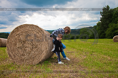Girl and boy pushing round bundle of straw. | High resolution stock photo |ID 3024346