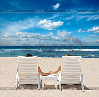Couple in beach chairs holding hands near ocean | High resolution stock photo |ID 3015406