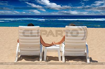 Para w leżaki trzymając się za ręce w pobliżu oceanu | Foto stockowe wysokiej rozdzielczości |ID 3015407