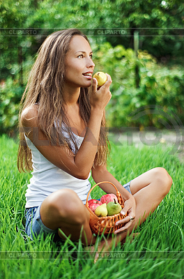 Piękna dziewczyna jedzenia gruszki na zielonej trawie | Foto stockowe wysokiej rozdzielczości |ID 3017232