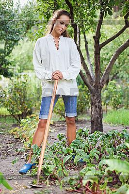 Junge Frau mit Hacke im Garten | Foto mit hoher Auflösung |ID 3017241