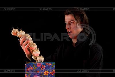 Erstaunter Vampir hält Geschenkbox mit Knoblauch | Foto mit hoher Auflösung |ID 3022242