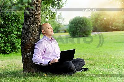 Biznesmen z laptopa siedzi w pobliżu drzewa | Foto stockowe wysokiej rozdzielczości |ID 3022054