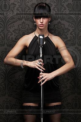 Sexy piosenkarka ma na sobie czarną sukienkę | Foto stockowe wysokiej rozdzielczości |ID 3024276