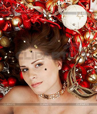 Piękna brunetka leżącego wśród dekoracji świątecznej | Foto stockowe wysokiej rozdzielczości |ID 3032442